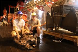 Christoph Beier und Bernd Schleifer mit einem Basalt vor dem TV-Greifer (S. Krumm, FAU)
