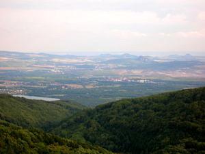 Blick vom Erzgebirgsrand nach Süden in das Becken des Egergrabens. Die dunklen Kuppen im Graben sind Reste abgetragener tertiärer Vulkane.